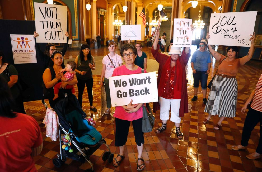 Protesters rally outside Iowa Gov. Kim Reynolds' formal office, May 4, 2018, at the Statehouse in Des Moines, Iowa.