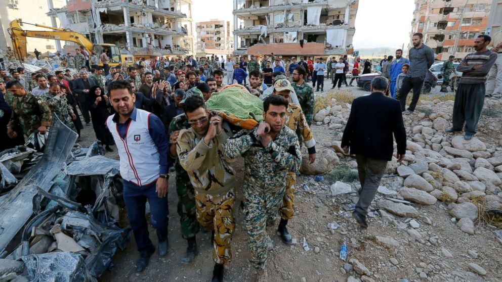 Iranian soldiers carry the body of an earthquake victim near the wreckage of a collapsed building in the city of Pole-Zahab, in Kermanshah Province, Iran, Nov. 13, 2017.
