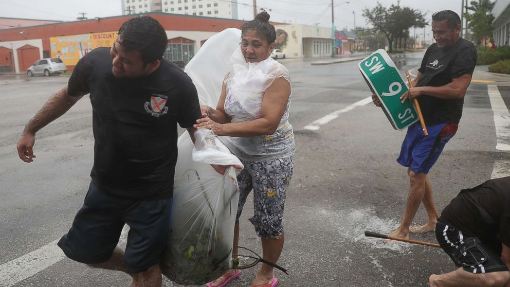 People clear debris out of a drainage ditch in an attempt to keep the area from flooding as Hurricane Irma passes through on Sept. 10, 2017 in Miami.