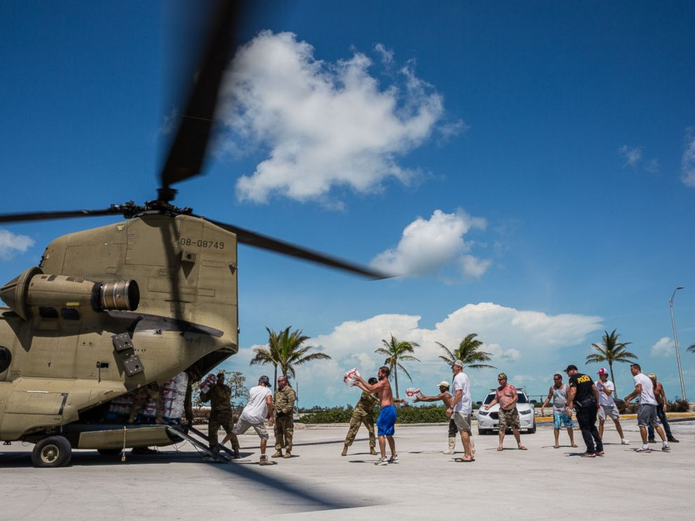 PHOTO: Soldiers with the Florida National Guard deliver food and water by a Chinook cargo helicopter that landed in a shopping center parking lot in Key West, Fla., Sept. 13, 2017.