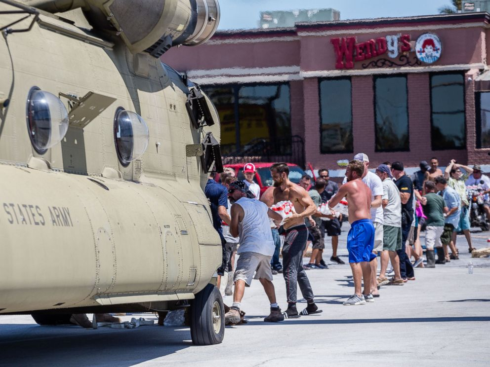 PHOTO: Local residents assist soldiers with the offloading of relief supplies from a Florida National Guard helicopter in Key West, Fla., Sept. 13, 2017.