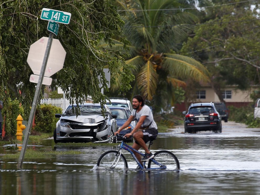 PHOTO: A man rides a bike on a flooded street following Hurricane Irma in North Miami, Sept. 11, 2017.