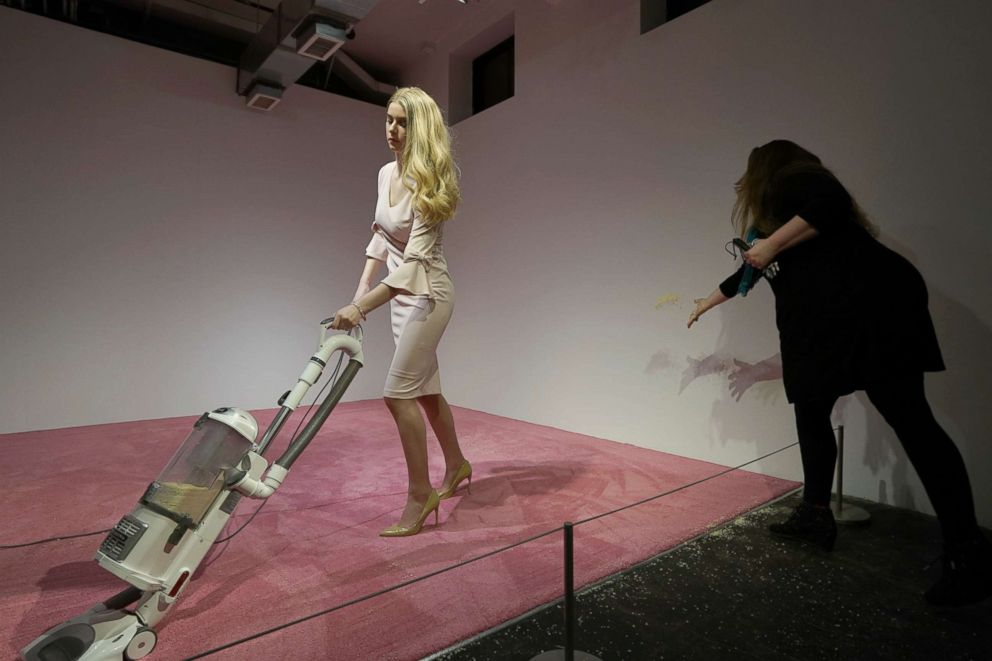 PHOTO: A spectator tosses crumbs for an Ivanka Trump lookalike to vacuum at Jennifer Rubells art exhibit Ivanka Vacuuming 2019 Feb. 5, 2019, at Flashpoint Gallery in Washington, DC.