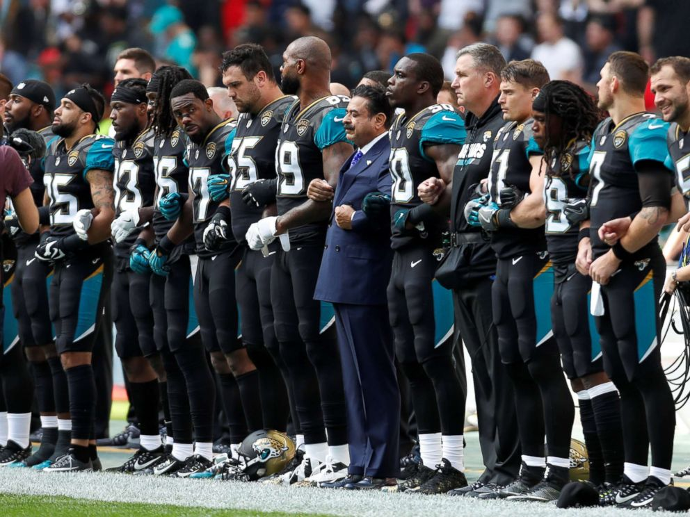 PHOTO: Jacksonville Jaguars owner Shahid Khan links arms with players during the playing of the U.S. national anthem before an NFL football game against the Baltimore Ravens at Wembley Stadium in London, Sept. 24, 2017.