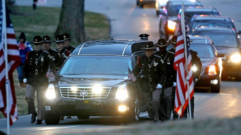 The honor guard walks along the hearse carrying the casket of Boone County Sheriff's Deputy Jacob Pickett, March 9, 2018, in Indianapolis.
