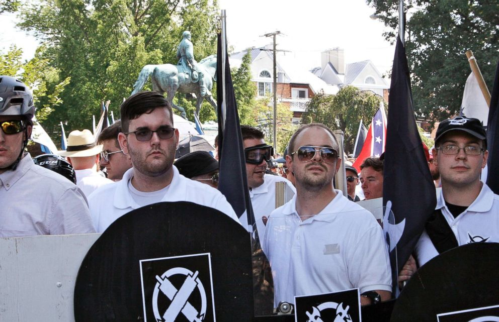 In this Aug. 12, 2017 photo, James Alex Fields Jr., second from left, holds a black shield in Charlottesville, Va., where a white supremacist rally took place.