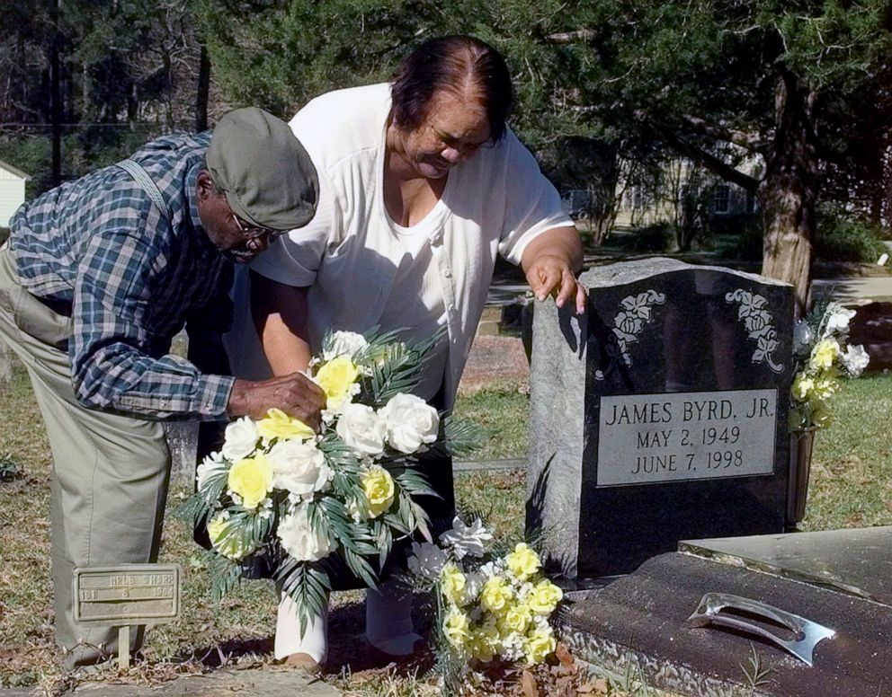 PHOTO: James Byrd Sr. and Stella arrange flowers around a new headstone commemorating their son, James Byrd Jr., Feb. 1, 1999, in Jasper, Texas.