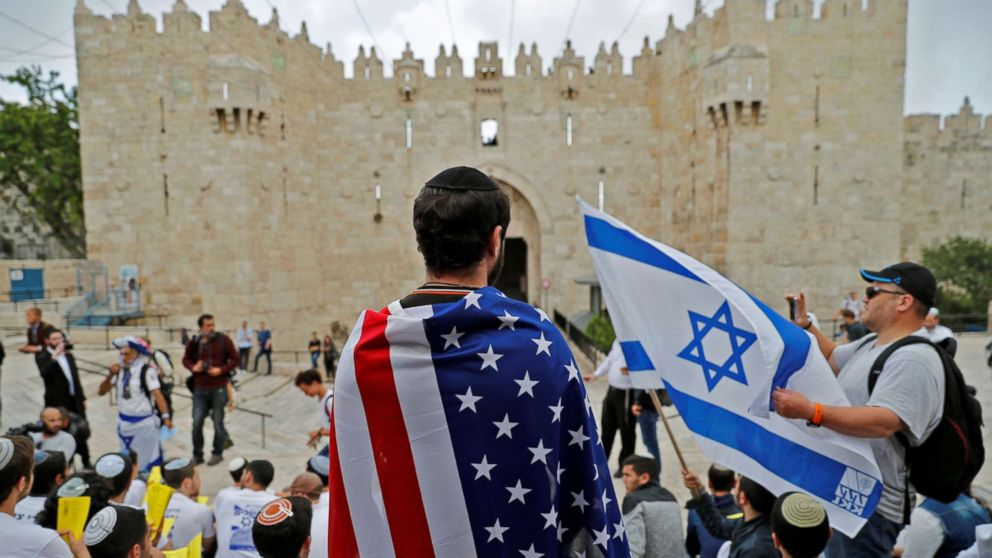 An Israeli man wears the US national flag at Damascus gate in Jerusalem on May 13, 2018, as Israeli nationalist settlers celebrate the Jerusalem Day in the Old City.