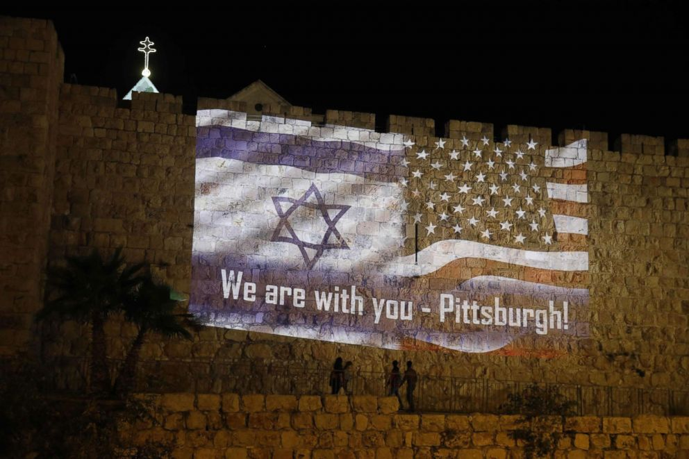 People walk under the U.S. and the Israeli flags projected on the walls of Jerusalem old city, Oct. 28, 2018, by the Jerusalem municipality to show solidarity with the Pittsburgh Jewish community following the shooting attack at the Tree of Life synagogue in Pittsburgh.