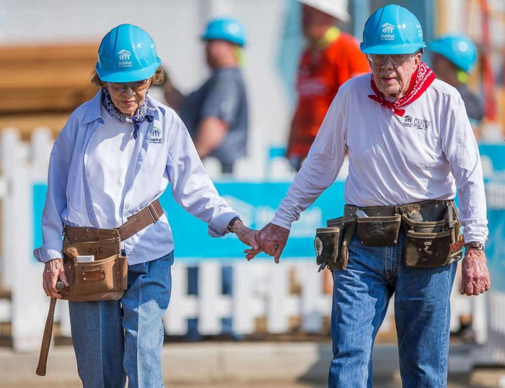 PHOTO: Former President Jimmy Carter holds hands with his wife, former first lady Rosalynn Carter, as they work with other volunteers at a work project with Habitat for Humanity, Aug. 27, 2018, in Mishawaka, Ind.