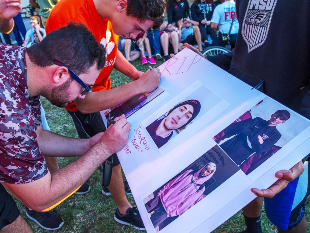 PHOTO: Students sign a poster with photos of Joaquin Oliver, one of the victims of a school shooting, during a candlelight vigil at the Amphitheater at Pine Trails Park, Parkland, Fla., Feb. 15, 2018.