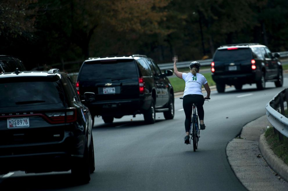 PHOTO: Juli Briskman gestures with her middle finger as a motorcade with President Donald Trump departs Trump National Golf Course, Oct. 28, 2017 in Sterling, Va.
