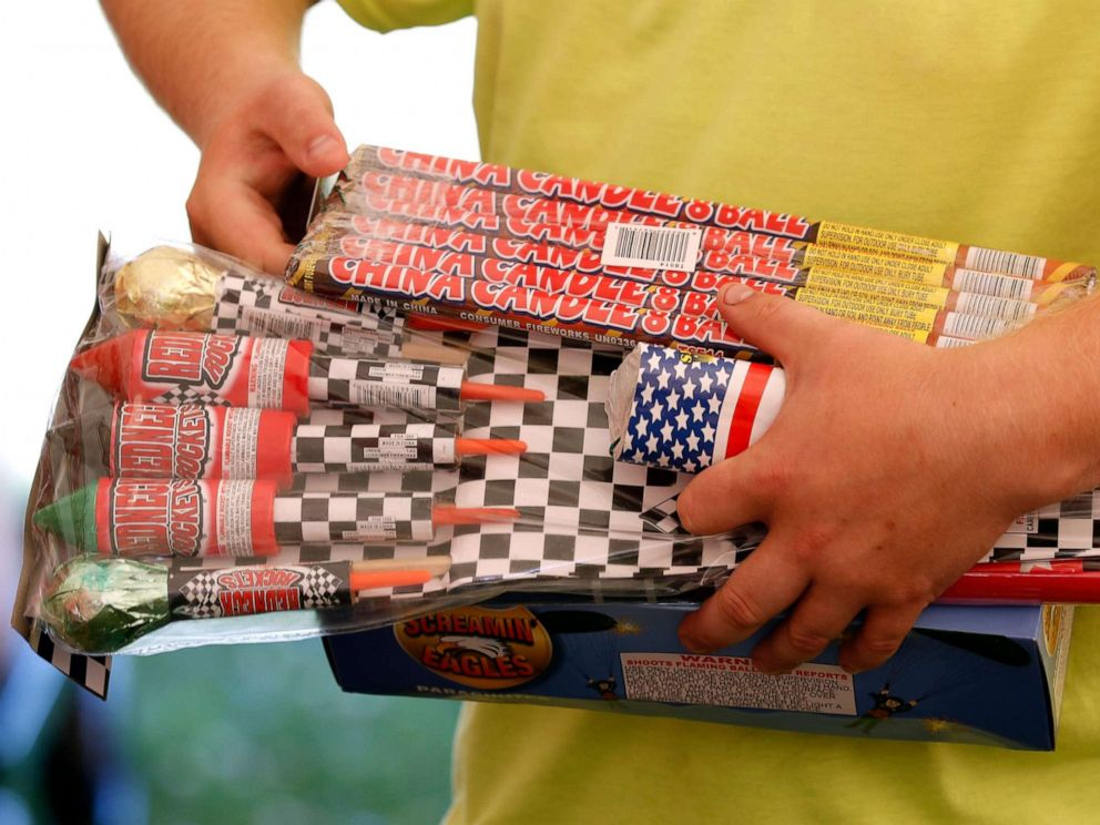 PHOTO: In this file photo, Julian Gibson holds packages of fireworks before buying them in a tent owned by the Iowa Fireworks Company, in Adel, Iowa, June 16, 2017.