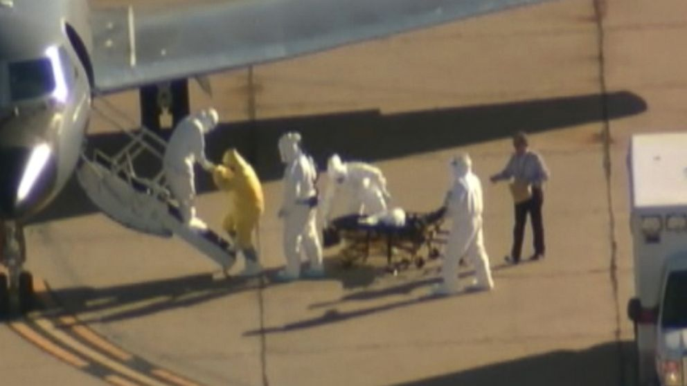 A man without a hazmat suit assists in the transportation of Ebola patient Amber Vinson from an ambulance to a plane at the Dallas airport on Oct 15, 2014.