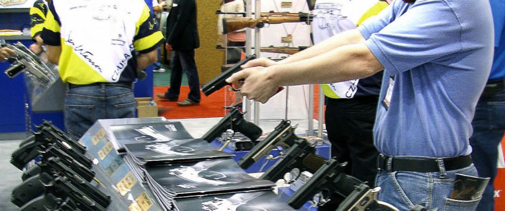 PHOTO: A U.S. National Rifle Association member holds a gun from a display at its convention in Kentucky.