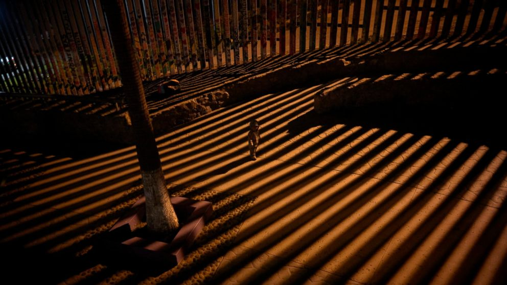 In this Jan. 11, 2019 photo, a boy plays as floodlights from the United States filter through the border wall in Tijuana, Mexico.