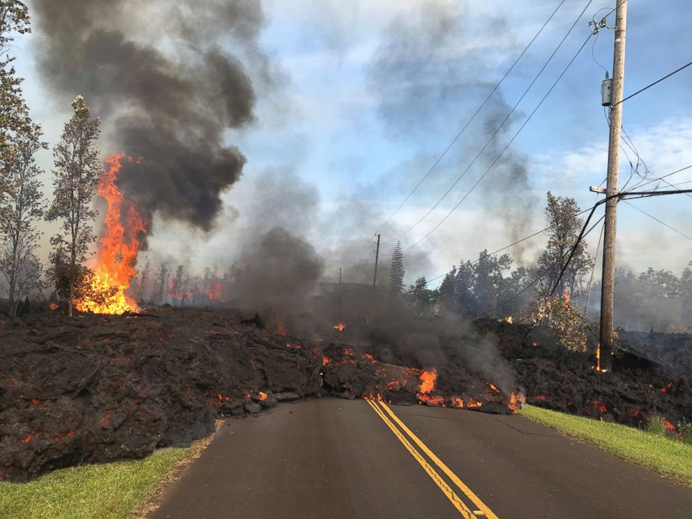 In this Saturday, May 5, 2018, photo provided by the U.S. Geological Survey, lava from Fissure 7 slowly advances to the northeast on Hookapu Street in the Leilani Estates subdivision in Pahoa, Hawaii.