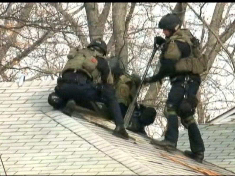PHOTO: Police officers swarm a home about four blocks from the Ferguson, Mo. police department as part of the investigation into the shooting of two police officers on March 12, 2015.