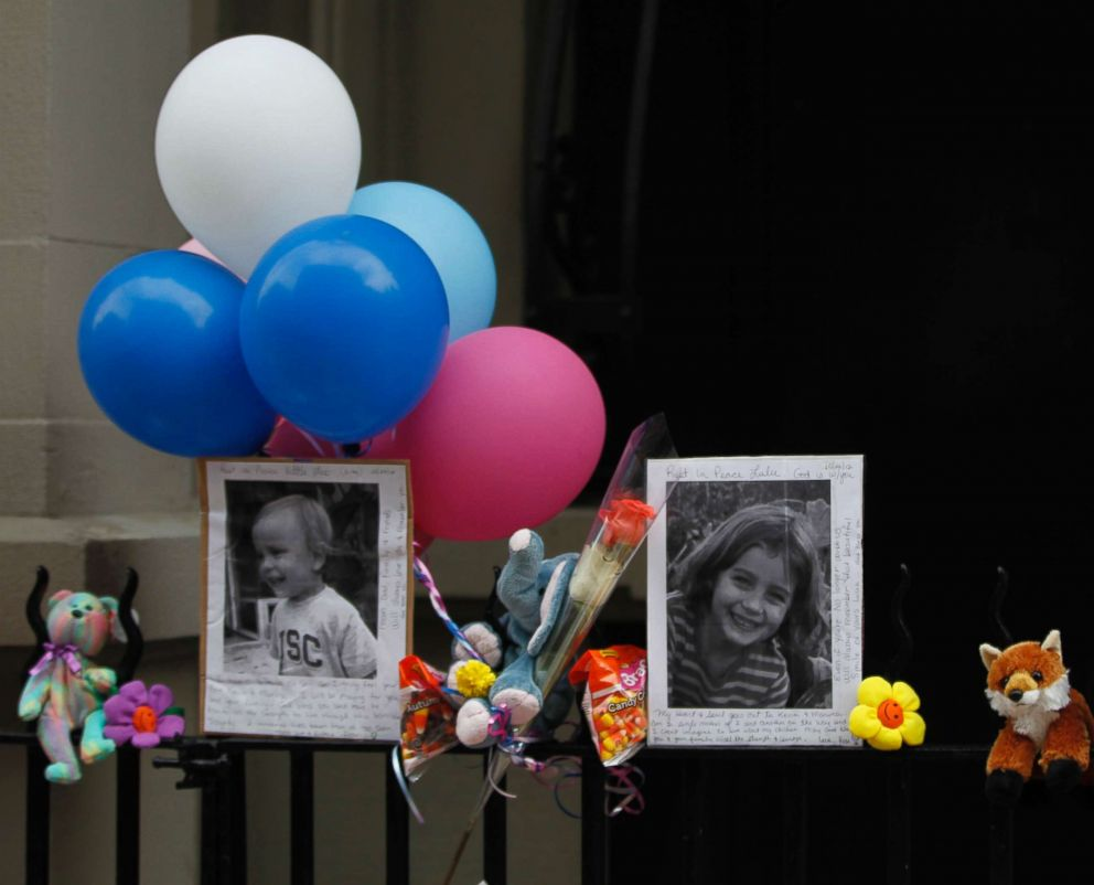 PHOTO: Photographs of the two children allegedly stabbed by their nanny are displayed alongside balloons and stuffed animals at a memorial outside the apartment building were they lived in New York City, Oct. 27, 2012.