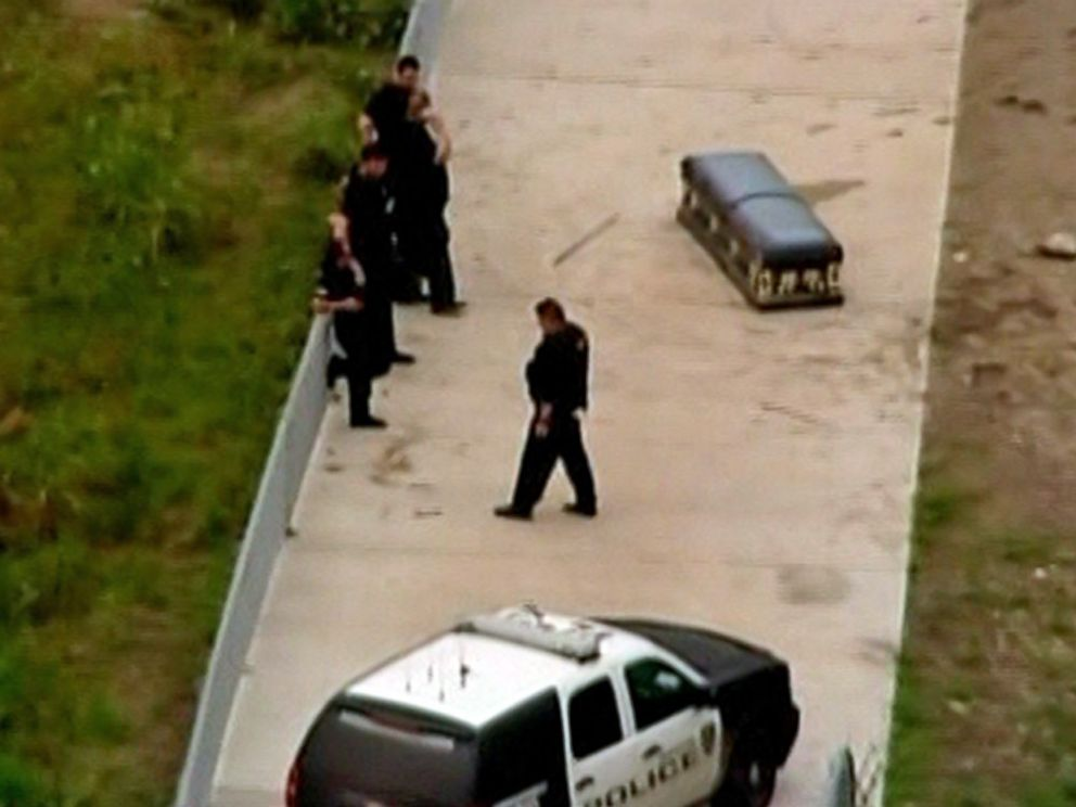 PHOTO: Police stand near a casket that authorities believe was unearthed from the Riceville Cemetery by recent flooding in Houston, Texas on May 26, 2015.