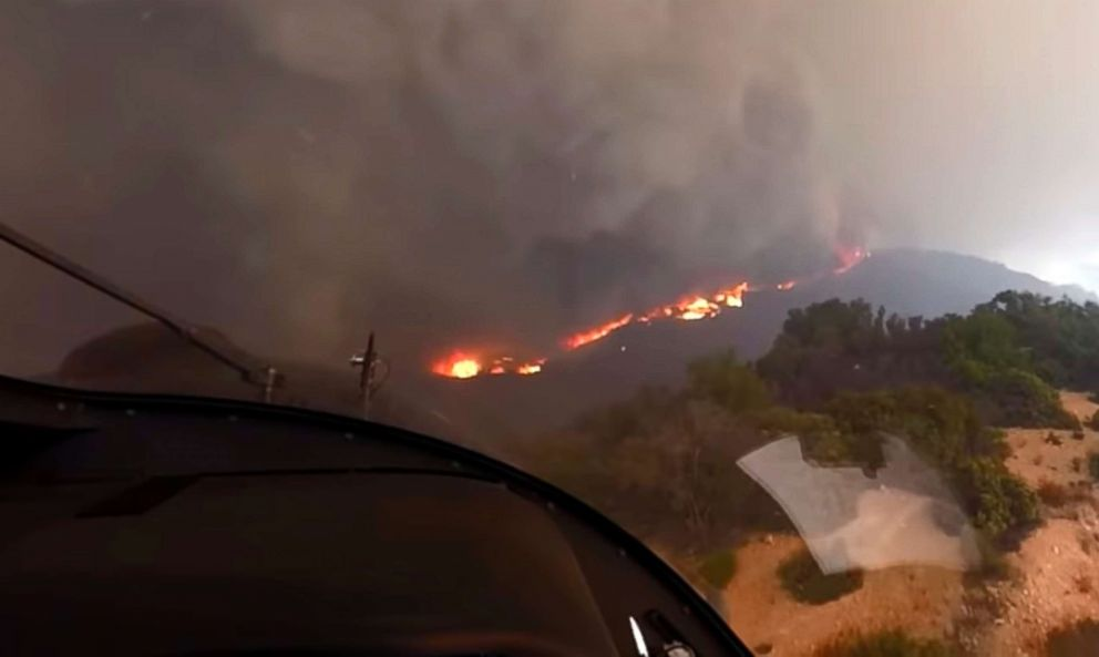 In this Nov. 9, 2018 photo from video provided by the Los Angeles Fire Department, LAFD Air Operations pilot David Nordquist records flames approaching as he takes off after rescuing three people and two dogs from Castro Peak in the Santa Monica Mountains in Malibu, Calif.
