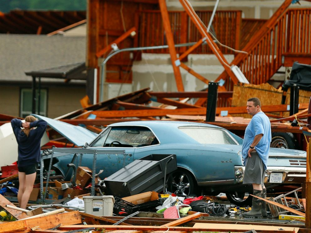 PHOTO: A man and woman inspect the damage to their home and classic cars after being hit by a tornado on Tuesday, May 28, 2019, in a neighborhood south of Lawrence, Kan., near US-59 highway and N. 1000 Road.