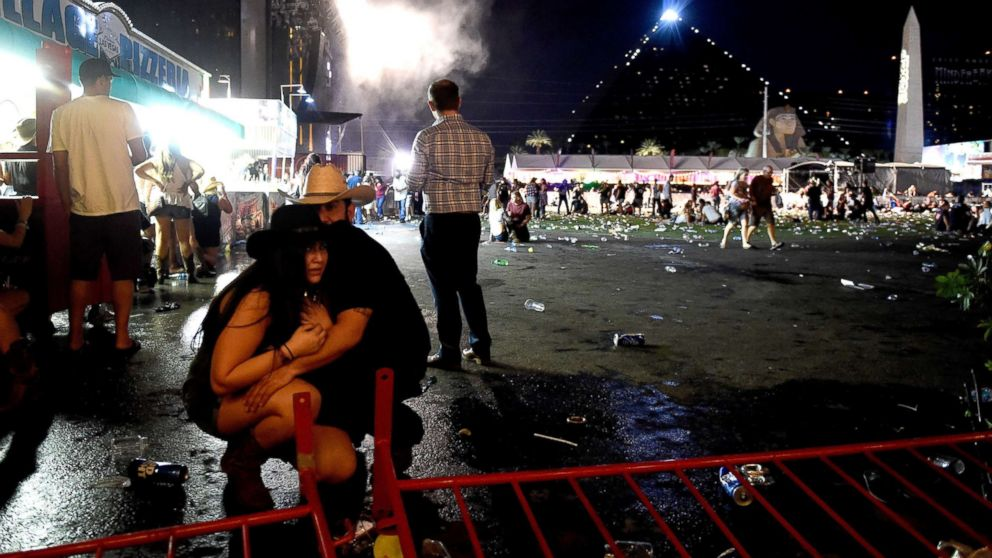 People take cover at the Route 91 Harvest country music festival after  gun fire was heard, Oct. 1, 2017 in Las Vegas, Nevada.