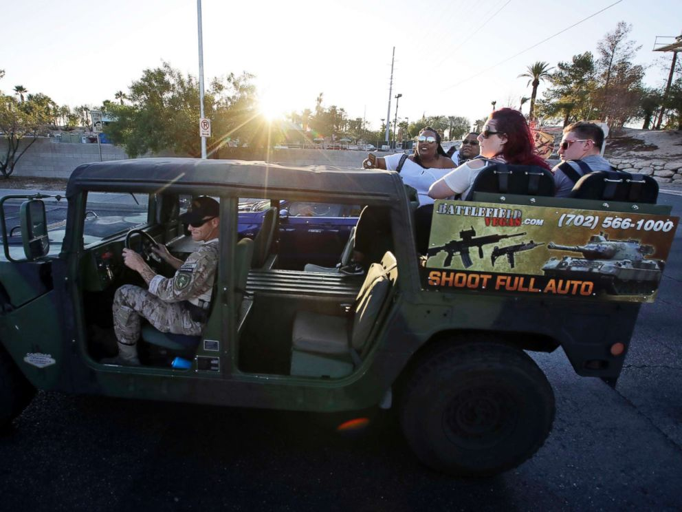 PHOTO: Tourists get a ride in a tour vehicle that also advertises gun range activities in Las Vegas, Oct. 2, 2017.