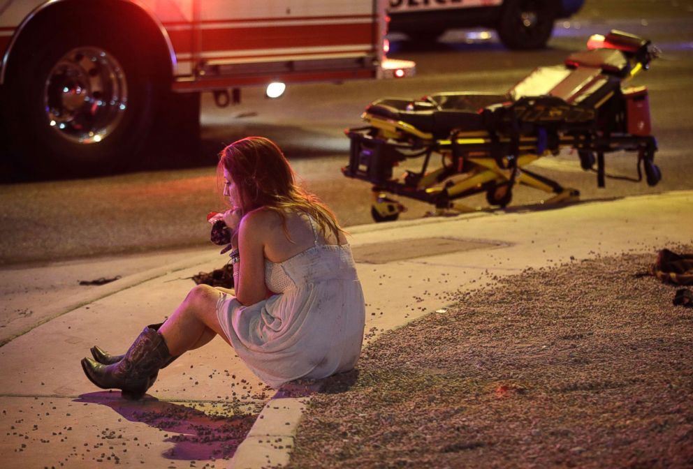 PHOTO: A woman sits on a curb at the scene of a shooting outside a music festival on the Las Vegas Strip, Oct. 2, 2017.