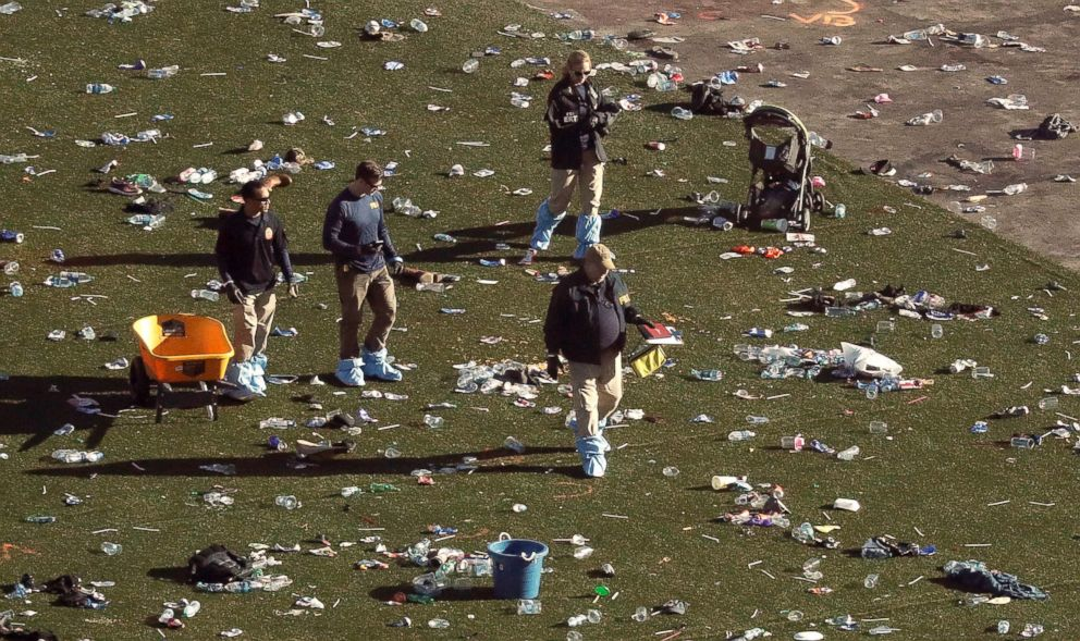 PHOTO: Investigators walk through debris on festival grounds across the street from the Mandalay Bay Resort and Casino, Oct. 3, 2017, in Las Vegas.