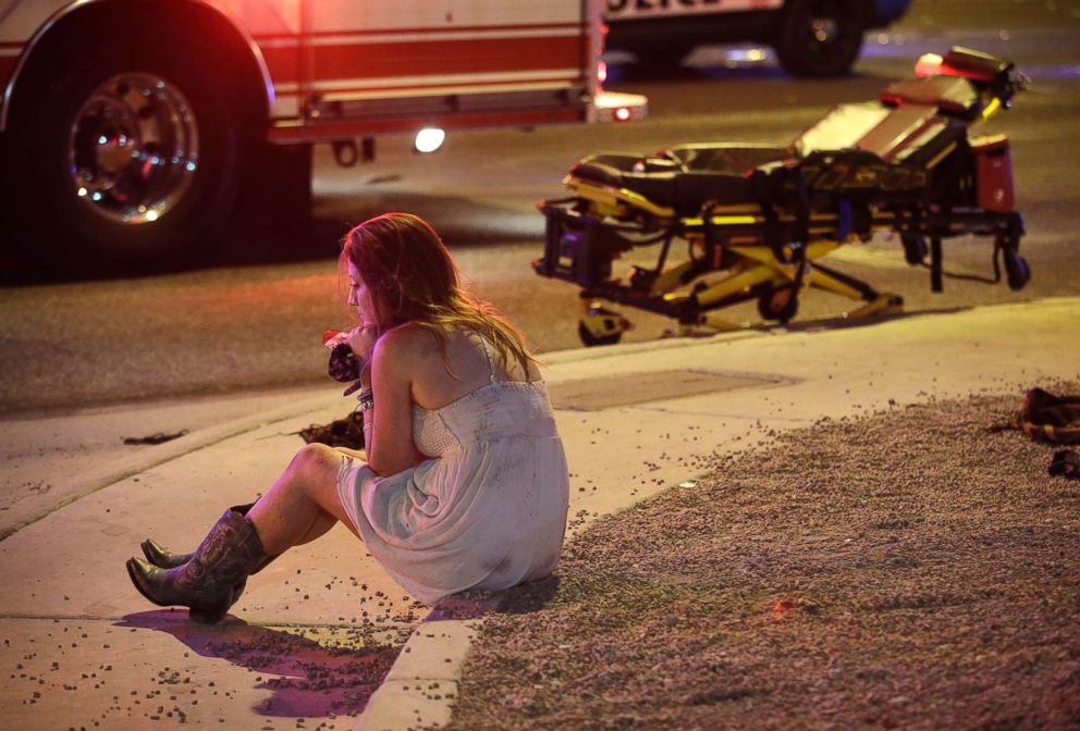 PHOTO: A woman sits on a curb at the scene of a shooting outside of a music festival along the Las Vegas Strip, Oct. 2, 2017, in Las Vegas.