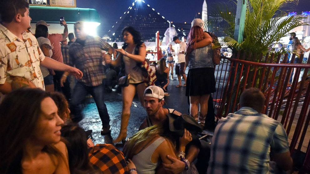 People run for cover at the Route 91 Harvest country music festival after gun fire was heard, Oct. 1, 2017 in Las Vegas.