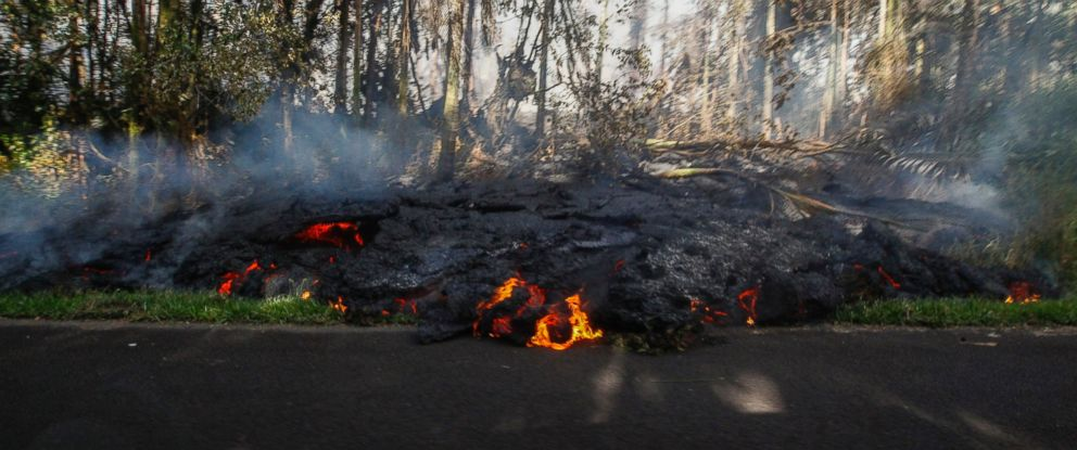 In this Sunday, May 6, 2018, photo, lava creeps onto the pavement on Luana Street in the Leilani Estates subdivision in Pahoa, Hawaii.