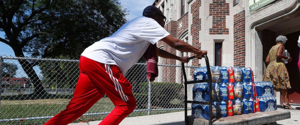 PHOTO: Teacher Cedric Cook pushes cases of water into Noble School in Detroit, Sept. 4, 2018.