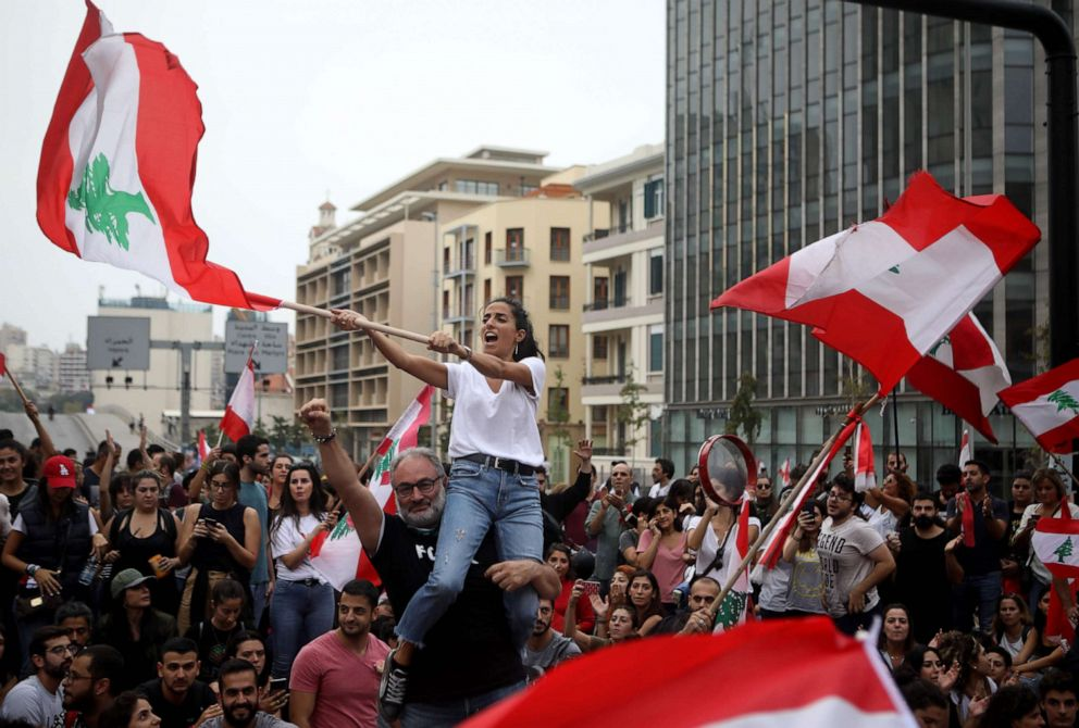 PHOTO: Lebanese protesters wave national flags during an anti-government demonstration in the centre of the capital Beirut, Oct. 26, 2019.