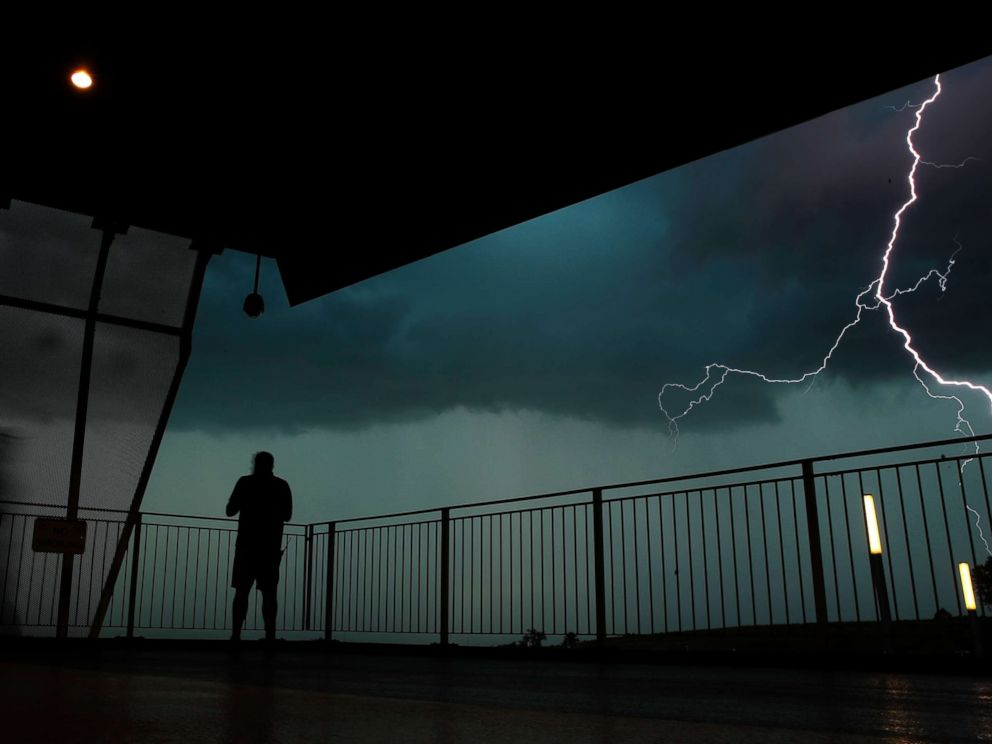 PHOTO: A man watches lightning from a concourse at Kauffman stadium during a severe storm before a baseball game, Aug. 28, 2018, in Kansas City, Mo.