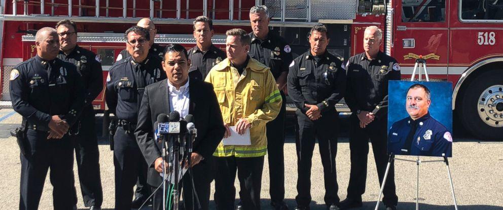Long Beach Mayor Robert Garcia stands near a photo of deceased Long Beach Fire Capt. Dave Rosa as he speaks in Long Beach, Calif., Monday, June 25, 2018.