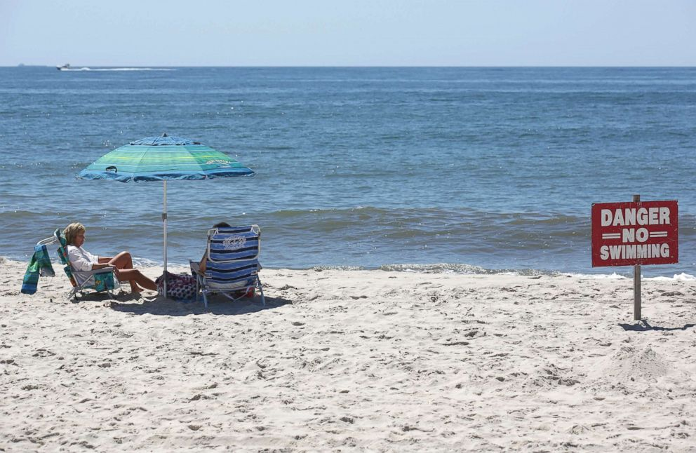 """A """"no swimming"""" sign is seen near Ocean Beach on Fire Island in Islip, N.Y., July 19, 2018. Two children were bitten in the leg in the waters off New York's Fire Island on Wednesday in possible shark attacks, prompting beach closings, authorities said."""