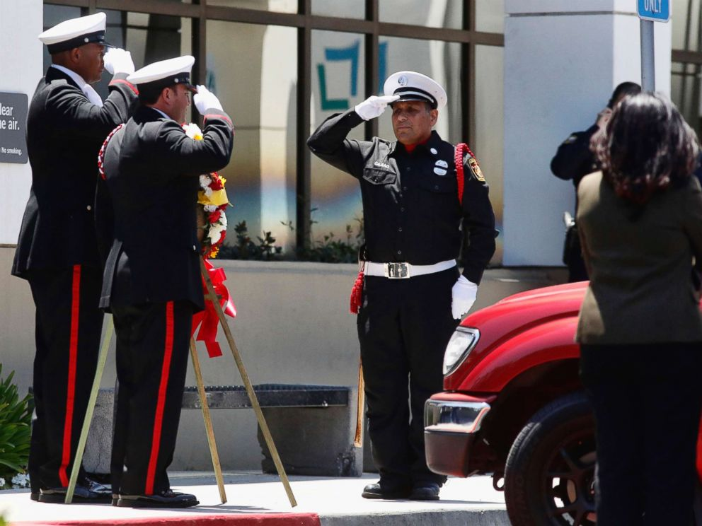 PHOTO: Long Beach firefighters salute for Fire Capt. Dave Rosa as they wait for his body to be transported from Saint Mary Medical Center in Long Beach, Calif., June 25, 2018.