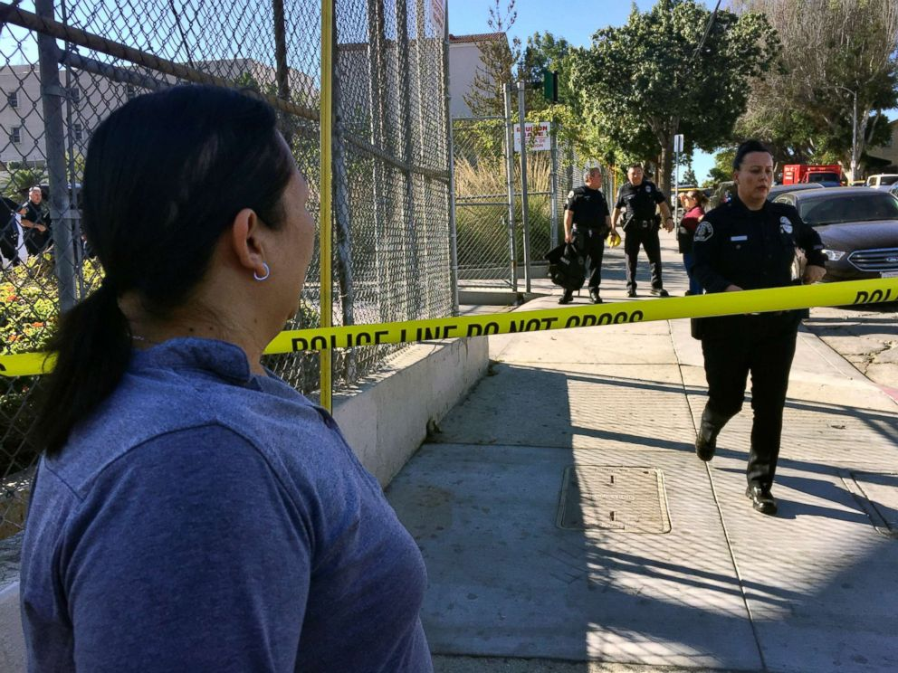PHOTO: Gloria Echeverria watches as Los Angeles police officers close off a street where a shooting occurred at a middle school in Los Angeles, Feb. 1, 2018.