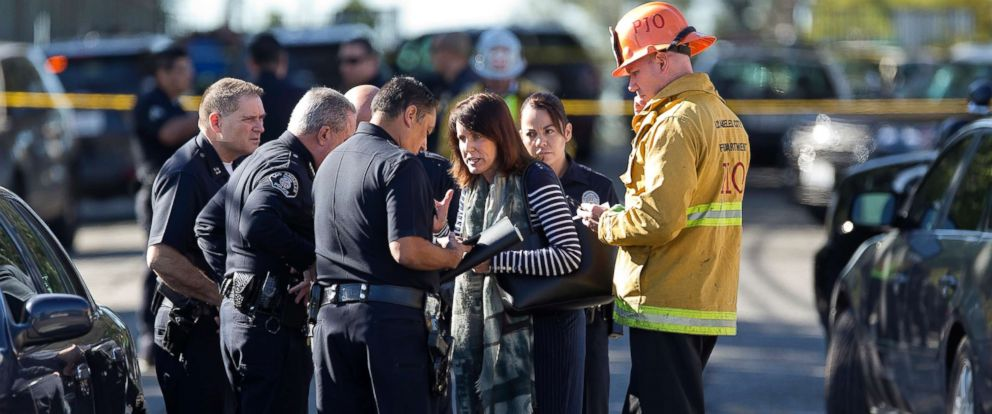 PHOTO: Los Angeles Fire departments Erik Scott, far right, police officers and school officials gather outside the Belmont High School in Los Angeles, Feb. 1, 2018.