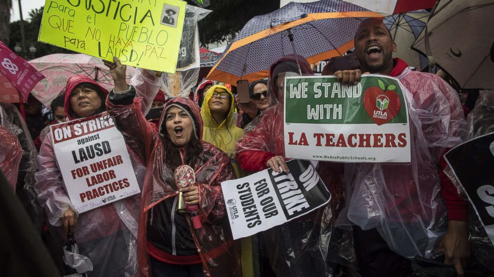 People rally in the streets of downtown in the pouring rain during a United Teachers Los Angeles strike on Jan. 14, 2019, in Los Angeles.
