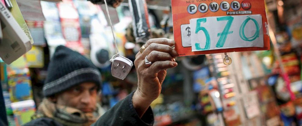 PHOTO: A vendor who sells lottery tickets hangs a sign for the Powerball drawing at a news stand in midtown Manhattan, Jan. 5, 2018.