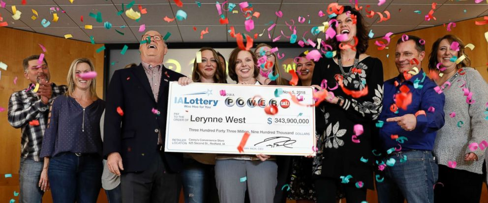 PHOTO: Iowa Lottery CEO Terry Rich, left, presents a check to Lerynne West, of Redfield, Iowa, center, for her share of a nearly $700 million Powerball prize, Nov. 5, 2018, at the Iowa Lottery headquarters in Clive, Iowa.