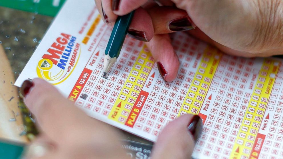A customer fills out a play slip before purchasing Mega Millions lottery tickets at a retailer in Arlington, Va., Oct. 22, 2018. No winning tickets were sold for 19 October's Mega Millions drawing, a 44-state lottery,  and the jackpot now grows to 1.6 billion US dollars for the next drawing on 23 October 2018.