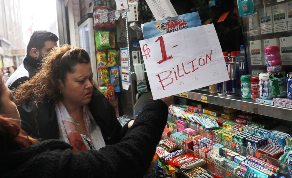 PHOTO: An impromptu One Billion dollars sign is on display as customers line up to buy Mega Millions tickets at a newsstand in midtown Manhattan in New York, Oct. 19, 2018.