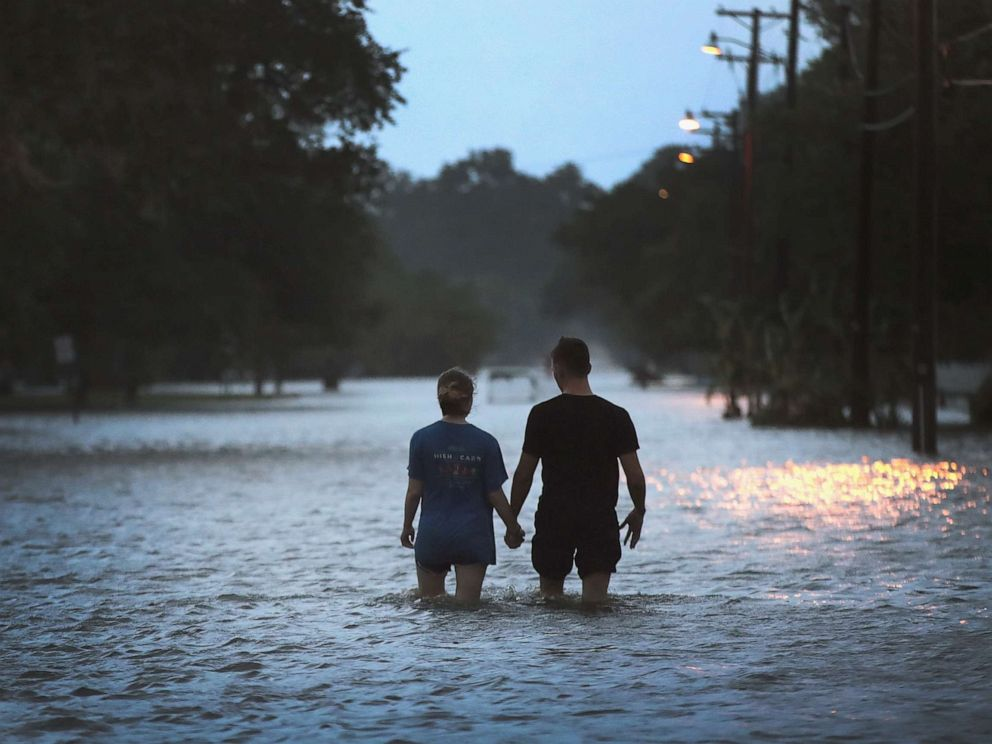 PHOTO: A couple strolls down Lakeshore Drive along the shore of Lake Pontchartrain after it was flooded in the wake of Hurricane Barry on Saturday, July 13, 2019 in Mandeville, La.