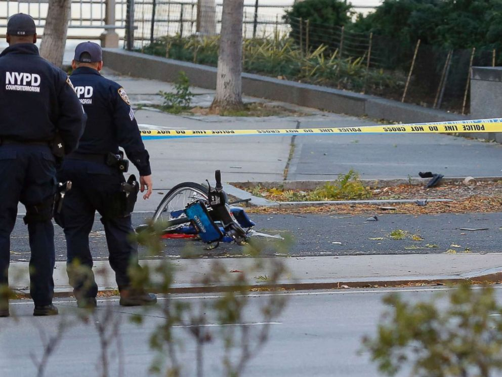 PHOTO: A New York Police Department officer stands next to a body covered under a white sheet near a mangled bike along a bike path, Oct. 31, 2017, in New York.