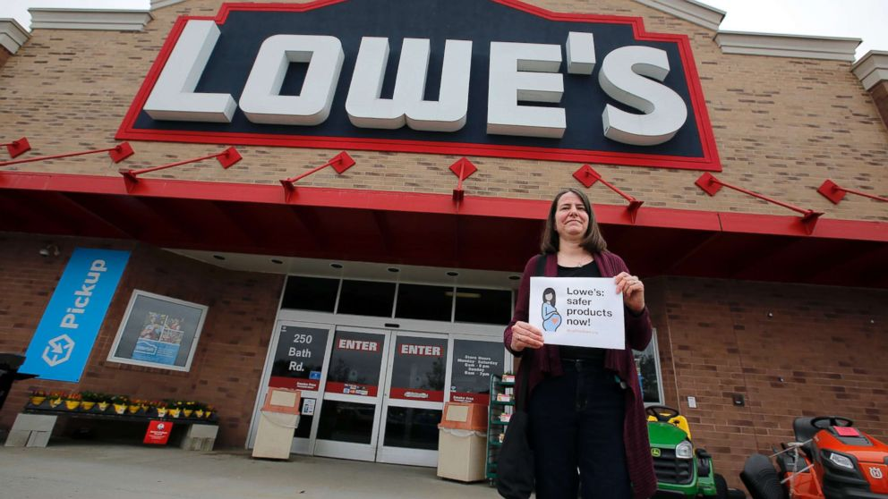 A woman holds a sign in front of a Lowe's store in Brunswick, Maine, while protests were held at several Maine locations in an effort to persuade Lowe's to discontinue the sale of paint strippers containing methylene chloride, May 10, 2018.