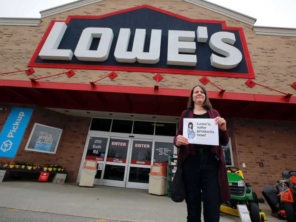 PHOTO: A woman holds a sign in front of a Lowes store in Brunswick, Maine, while protests were held at several Maine locations in an effort to persuade Lowes to discontinue the sale of paint strippers containing methylene chloride, May 10, 2018.